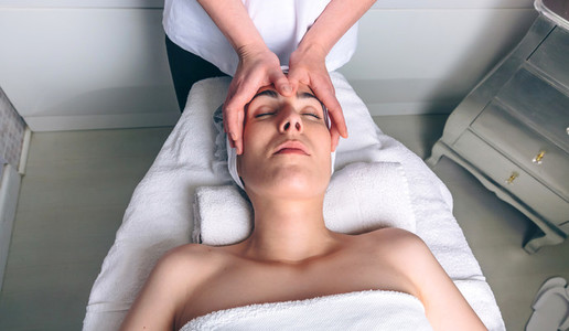 Woman receiving facial treatment on clinical center