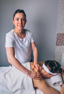Female massage therapist doing treatment to woman in clinic