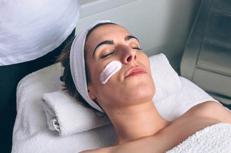 Woman lying with facial mask treatment in spa