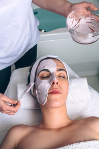 Beautician applying facial mask to woman in spa