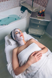 Relaxed woman lying with facial mask in spa