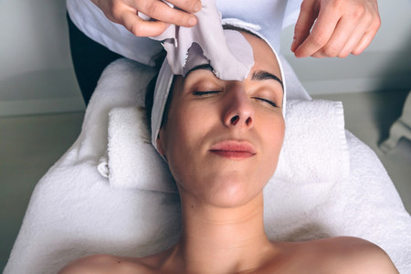 Woman lying while removing facial mask treatment in spa