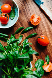 Lifestyle photo of cooking healthy eating with tomatoes and fresh spinach on a kitchen table