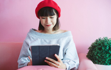 Young happy asian millennial woman using digital tablet at the p