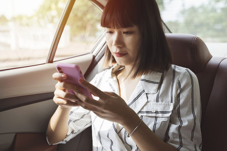 woman using phone at car