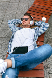 Young man with headphones and tablet outdoors