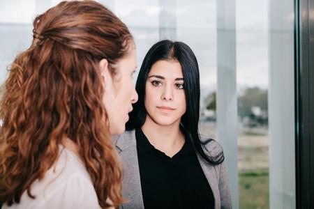 Two business women talking near a window in the office