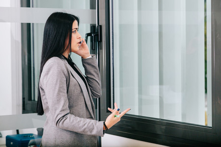 A businesswoman talking by cellphone near a window in the office