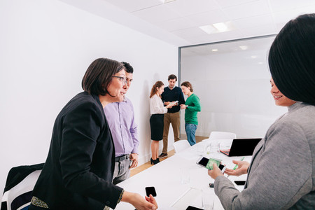 Group of office workers at a meeting standing around the boss