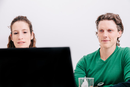 Close up of two office worker sitting watching the laptop