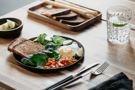 Healthy breakfast with fried egg  avocado  toasts  beans and fresh spinach on a wooden table