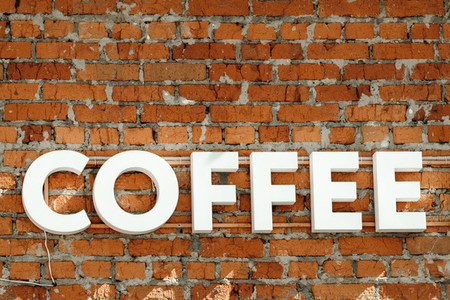 Sign of coffee on a brick wall