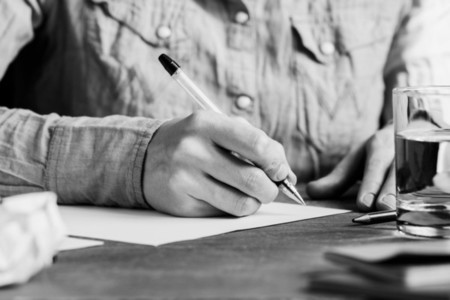 The man is writing on a white paper sheet in a workplace The concept of a work and education Black and white photography