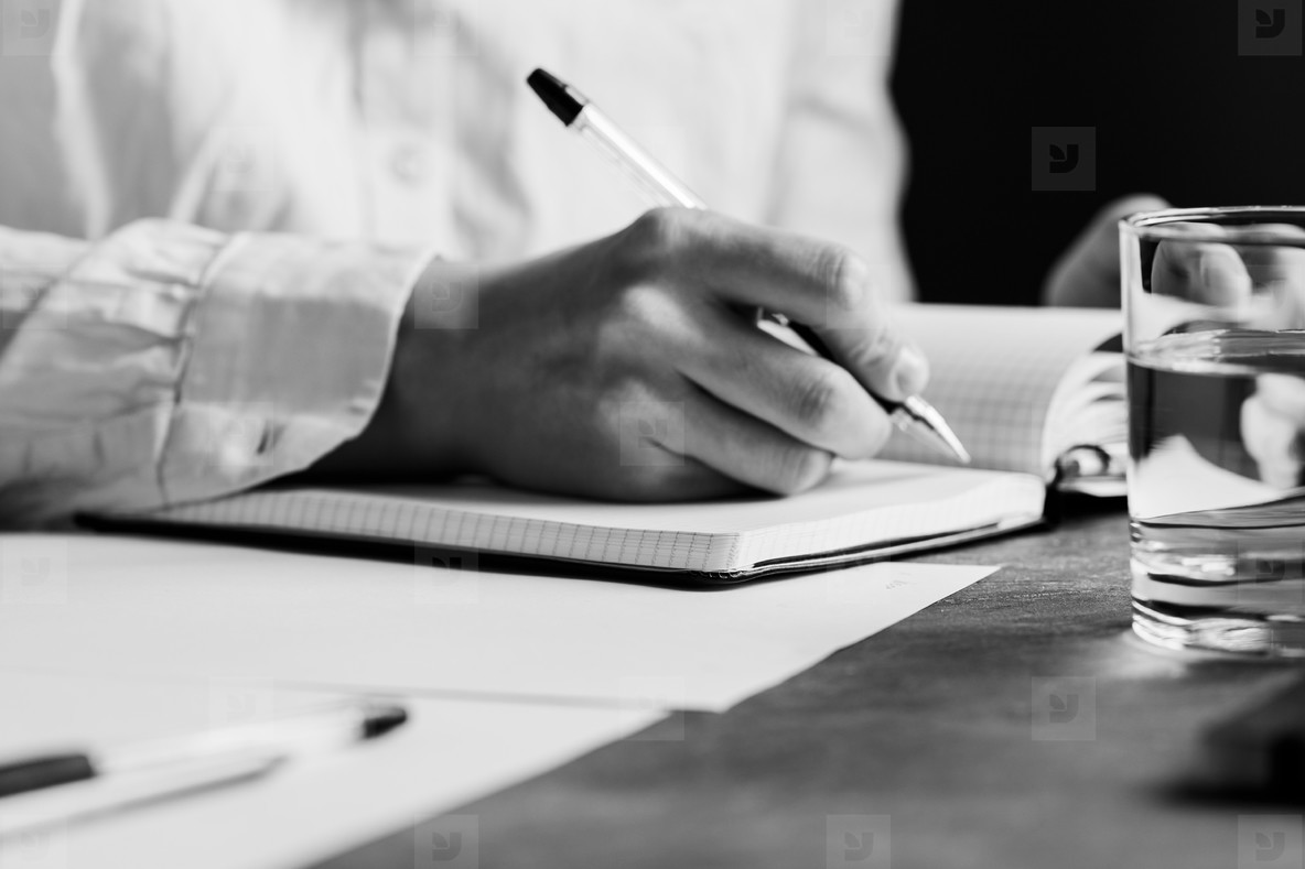 The man is writing in a notebook in a workplace  The concept of a work and education  Black and white photography