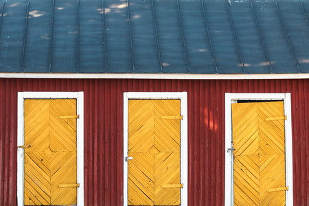 Three vintage yellow doors in a red wooden house with blue roof  Scandinavian design