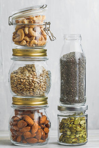 Various nuts and seeds in glass jars over white wooden table against white background The concept of vegetarian and organic food Set of photos