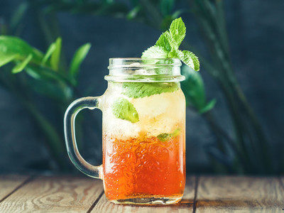 Ice black tea in a glass jar with fresh mint on a wooden table