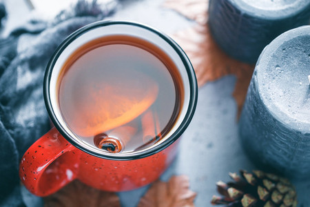 Winter season hot tea in a red ceramic mug surrounded by black aromatic candles warm scarf maple leaves on a concrete grey background The concept of cosy holidays and New Year