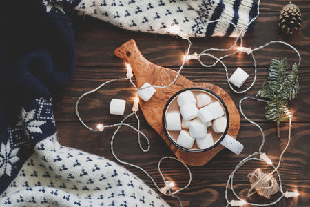 Hot cocoa with marshmallow in a white ceramic mug surrounded by winter things on a wooden table The concept of cosy holidays and New Year Top view flat lay