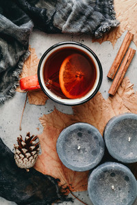Autumn flat lay composition on a grey concrete background Maple leaves season tea with spices black aromatic candles and warm scarf Top view