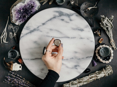 Witchs hand holding Smoky quartz above a marble white round tray  The place for witchcraft with magic things around  View from above