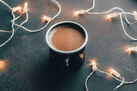 Close up view on a coffee on a table among festoon lights The concept of cosy home and winter Holidays