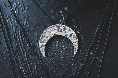Silver female necklace in shape of Moon Crescent on a black background The concept of magic and witchcraft