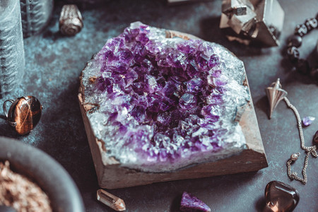 Amethyst Druze on a witchs altar for a magical ceremony among crystals and black candles