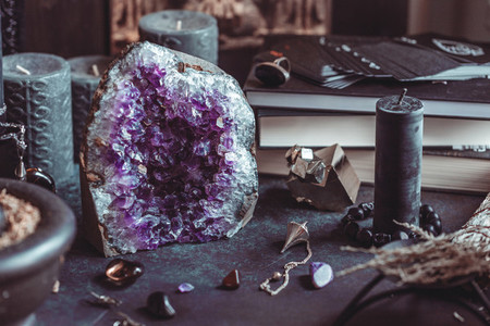 Amethyst Druze on a witchs altar for a magical ritual among crystals and black candles