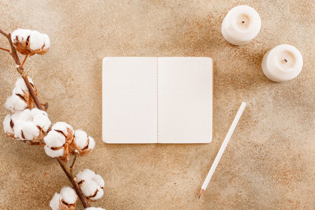 Open notebook with white pencil among cotton flowers branch and white candles  Flat lay  top view  cmock up  The concept of planning and goals to set on New Year