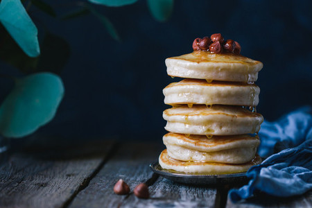 Stack of pancakes with honey and nuts
