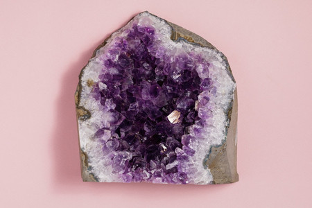The amethyst stone on pastel pink background  Minimalism flat lay style