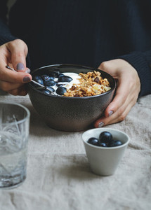 Close up of breakfast table The womens hands is holding the bowl of granola
