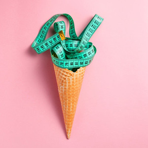The concept of diet and healthy lifestyle  Green measuring tape in the waffle cone on the pastel pink background