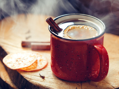 Mulled wine in a red ceramic mug over rustic wooden boards surrounded spices