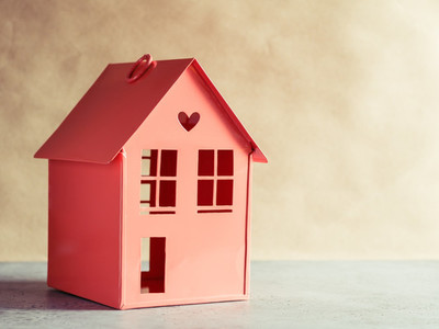 Metal red model of a house with a heart  The concept of home and domestic life  Copy space