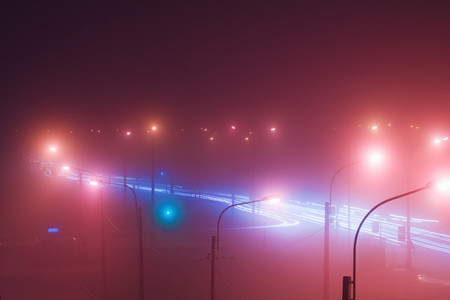 Neon lights of night city and motion traffic in fog Retro colored image