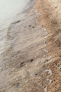 Close up shot of water on a sandy beach on sunny day