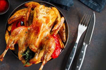 Roasted guinea fowl with herbs and olive oil on a dish with a garnish of potatoes and red pepper