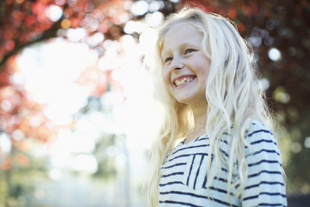 Confident happy girl smiling in autumn park