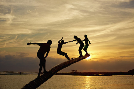 Silhouette carefree kids playing on tree trunk over sunset ocean