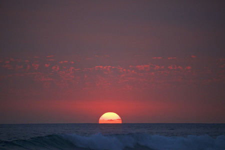 Sunset in red sky over ocean horizon