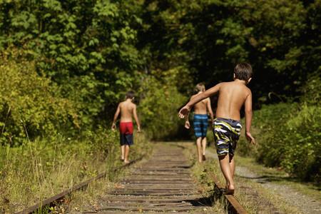 Boys in swim trunks walking along sunny railroad tracks in woods