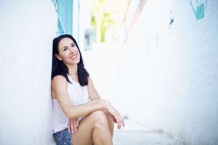 Portrait smiling confident woman relaxing in summer alley
