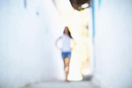 Defocused view woman walking in alley
