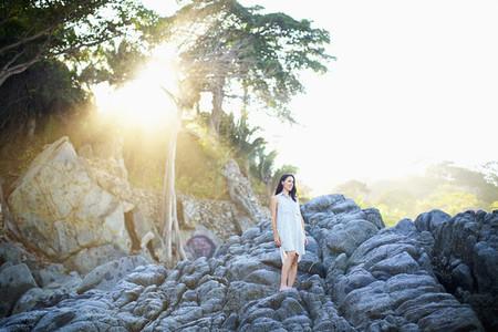 Serene woman standing on rocks under sunny tree