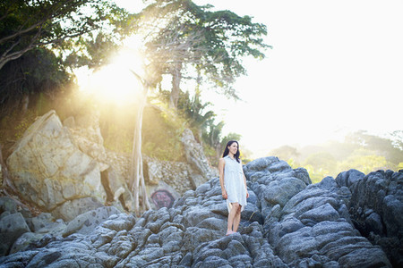 Serene woman standing on rocks under sunny tree