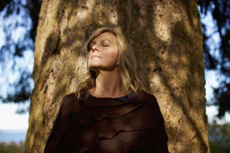 Portrait serene woman with eyes closed standing at sunny tree trunk