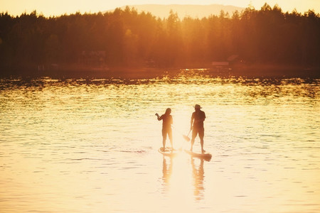 Silhouette couple standup paddleboarding on sunny sunset lake