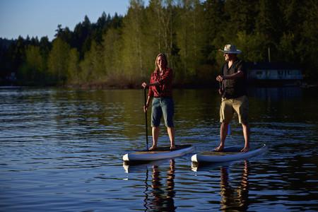 Couple standup paddleboarding on sunny lake  Shawnigan Lake
